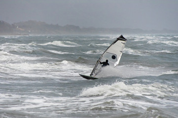 windsurf with white sail jibes on a wave in a winter cold day