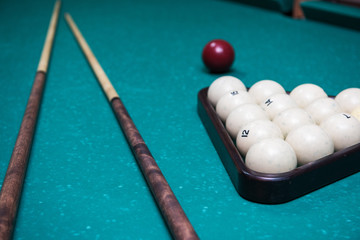 Russian billiard table with balls and cue sticks on a green background