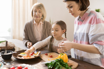 Little girl putting pieces of fresh vegetables on toast while helping her mom and granny with sandwiches for breakfast