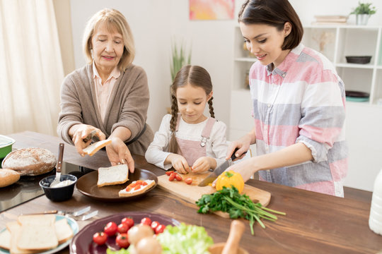 Young woman cutting tomatoes on board while her daughter and mother making sandwiches in the kitchen