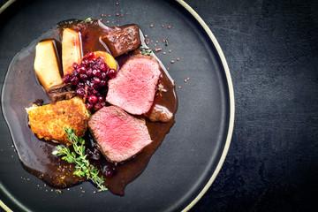 Traditioneller Hirschrücken mit gebratenem Kartoffel Püree und Früchten in Wild Rotwein Sauce als Draufsicht auf einem Modern Design Teller mit Textfreiraum rechts