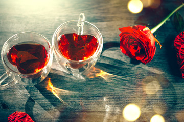St. Valentine's Day scene. Valentine heart shaped tea cups with red hearts rattan decor and red rose on wooden background. Dating
