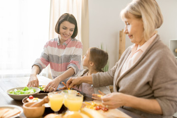 Happy young mother and her little daughter having talk in the kitchen while cooking breakfast together