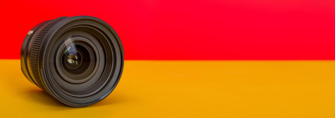 Professional Camera Lens on red and yellow background template