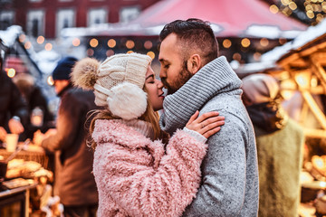 An attractive couple in love, cuddling together and kissing at the winter fair at a Christmas time.