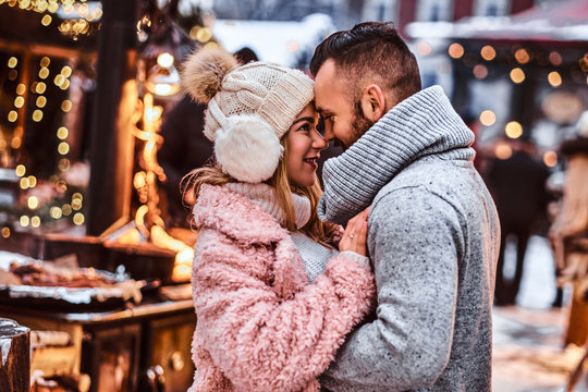 An attractive couple in love, a stylish couple wearing warm clothes cuddling together and looking each other at the winter fair at a Christmas time.