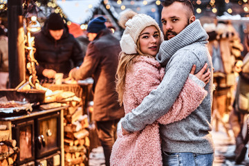 A charming couple in love, hugging together and looking at a camera while standing at the winter fair at a Christmas time