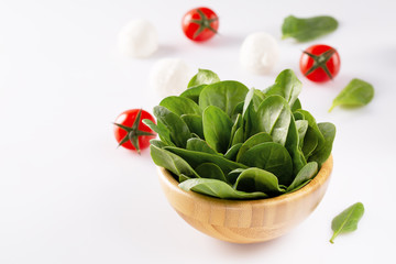 Fresh baby spinach in a wooden bowl on white background.
