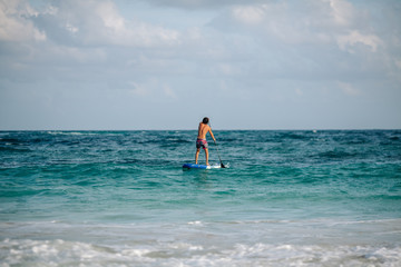 Man sails surfing on the waves in the Caribbean, in Cancun, Mexico