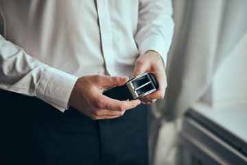 Businessman putting on a belt, fashion and clothing concept,groom getting ready in the morning before ceremony