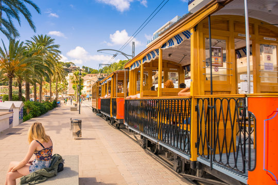 Famous old train in Port de Soller in Mallorca full of motor boats and buildings on cliffs