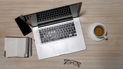 Desk with laptop, eyeglasses, notepad, smartphone, pen and a cup of tea on a wooden table. Top view with copy space. Flat lay - image
