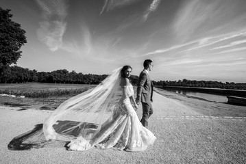 Black and white photo of beautiful stylish newlyweds that strolling on their wedding day. Wedding day