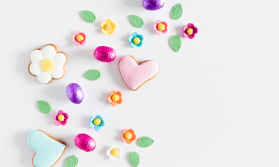 Easter eggs, cookies, sweets, easter decorations on white background. Minimum Easter holiday concept. Flat lay, top view, copy space