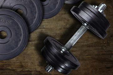 Dumbbell and weights on a wooden background.