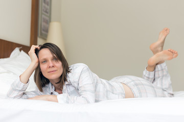 Woman with beautiful eyes and broad smile lying on bed in bedroom wearing pyjamas