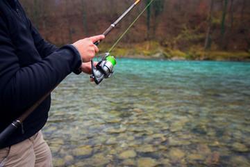 Fisherman`s hand holding fishing rod