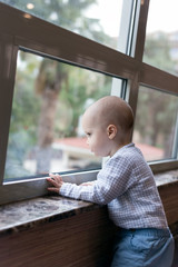 Lovely little baby boy looking outside through the window