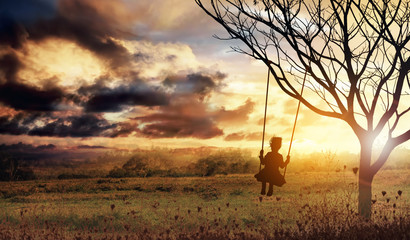 Silhouette of girl on swing at sunset
