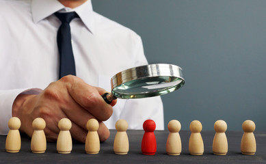 Recruiter looking through magnifying glass on candidates. Hiring and recruiting.