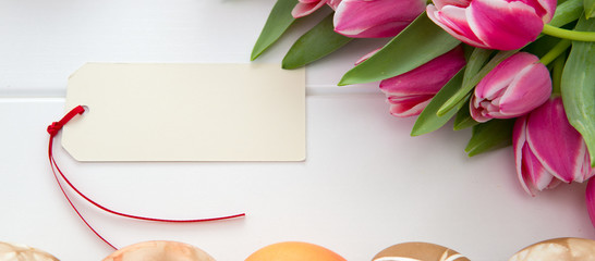 Easter card with bouquet of pink tulips and colorful eggs on white wooden .