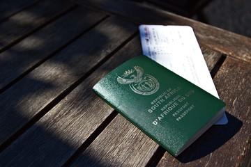 A South African passport and a plane ticket. Travel or immigration concept image.