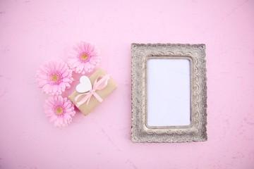 Hintergrund für Muttertag, Hochzeit, Valentinstag - Geschenk mit Blumen rosa und Bilderrahmen leer
