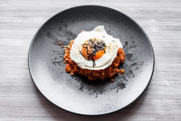 Kimchi bokkeum bap on black plate on wooden board