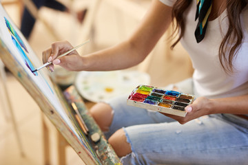 Girl in glasses dressed in white t-shirt and jeans with a scarf around her neck paints a picture in the art studio