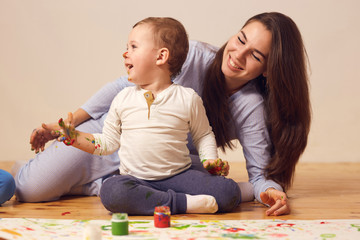 Happy mother and her little son with paints on his face dressed in home clothes are sitting on the wooden floor in the room and painting with fingers on the white paper