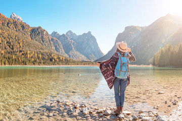 Happy young traveler woman having fun on a coast of a Dobbiaco lake in Dolomites Alps, Italy