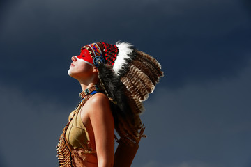 A young woman plays the part of a native Indian  woman. Dressed as a native Indian wearing a feathered  headdress. She poses outdoors in a nature surrounding.