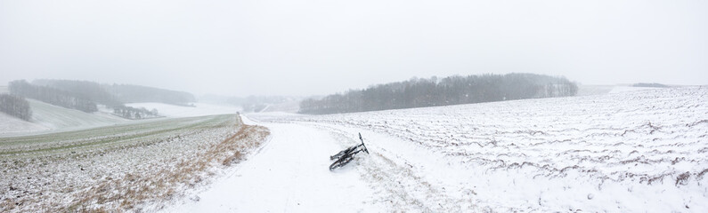 Snow field and dirty road  and bike panorama