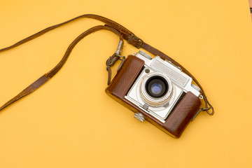 Vintage Camera with A Leather Strap Hanging on Yellow