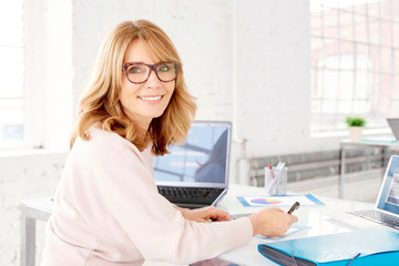 Portrait of attractive smiling businesswoman sitting at office desk and looking camera while doing some papework, copy
