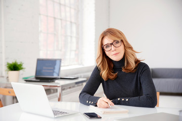 Businesswoman sitting at office desk and doing some paperwork