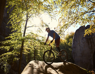 Young male cyclist balancing on trial bicycle, making acrobatic trick on big boulder in the forest on summer sunny day. Concept of extreme sport active lifestyle