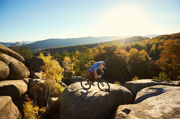 Athlete male cyclist balancing on trial bicycle, making acrobatic trick on top of big rock on summer evening, blue sky, forest and sunset on background. Concept of extreme sport active lifestyle