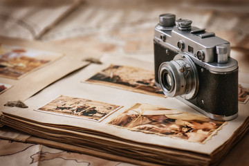 Photo album with a camera on the background of old vintage maps