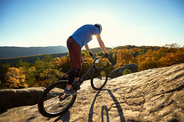 Man cyclist riding on trial bike, rider making acrobatic trick on top of big boulder on summer evening, blue sky, forest and sunset on background. Concept of extreme sport active lifestyle