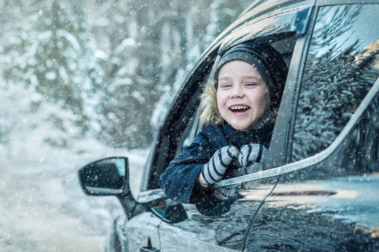 Happiness caucasian smiling boy looking out of black car window in winter sunny day