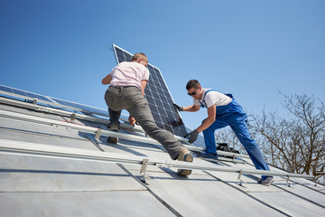 Male workers installing stand-alone solar photovoltaic panel system. Electricians mounting blue solar module on roof of modern house. Alternative energy innovation environmental ecology concept.