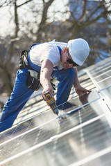 Male engineer installing stand-alone solar photovoltaic panel system using screwdriver. Electrician mounting blue solar module on roof of modern house. Alternative energy ecological concept.