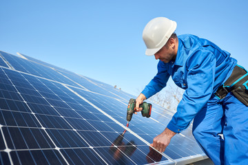 Man worker in blue suit and protective helmet installing solar photovoltaic panel system using screwdriver. Professional electrician mounting blue solar module. Alternative energy ecological concept.