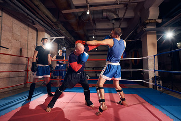 Athlete man boxer training kickboxing with trainer in the ring at the sport club