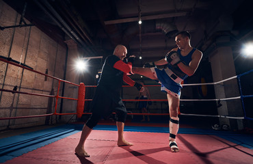 martial muscular fighter exercising mma with his trainer in the ring at the health club