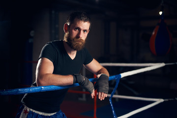 Portrait of young male professional boxer standing in the ring at the health club after hard training boxing