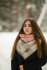 Portrait of a girl playing with snow in winter.