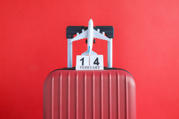 Luggage with valentines day date calendar and aircraft on red background minimalistic vacation concept.