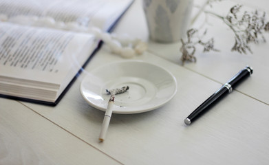 Smoking cigarette, book and mug on a white wooden table